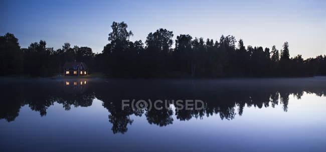 Маленькій Хатині з освітлені вікна на озеро вночі — стокове фото