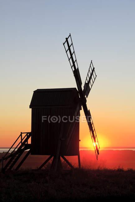 windmill silhouette at illuminated sunset sky stock photo 187606676