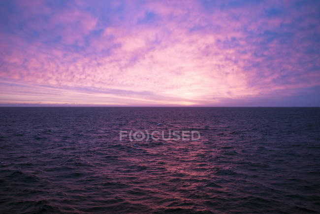 Pink sunset sky with clouds over water — Stock Photo