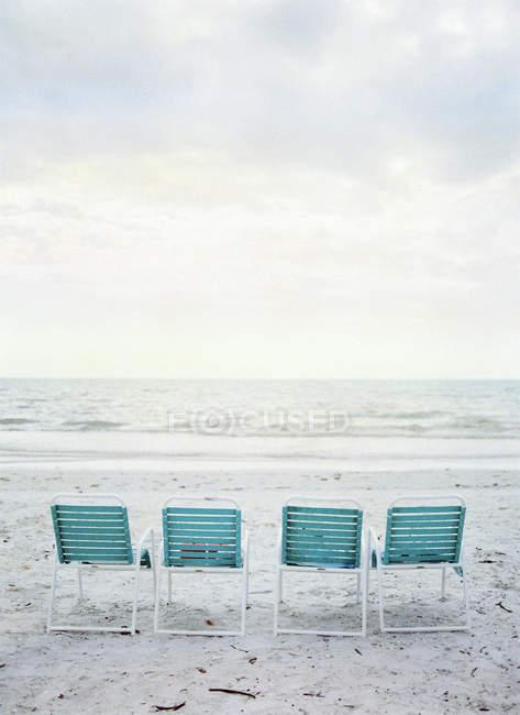Четыре пустые складные стулья на пляже — стоковое фото