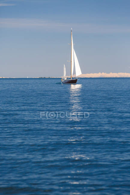 Scenic view of man traveling by sailboat on sea — Stock Photo