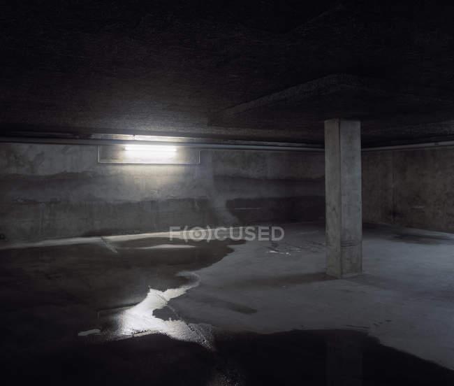Пустая подземная парковка с мокрым полом — стоковое фото