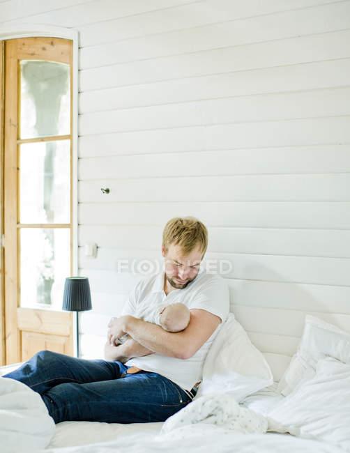 Mittlerer erwachsener Mann hält Baby im Schlafzimmer in den Armen — Stockfoto