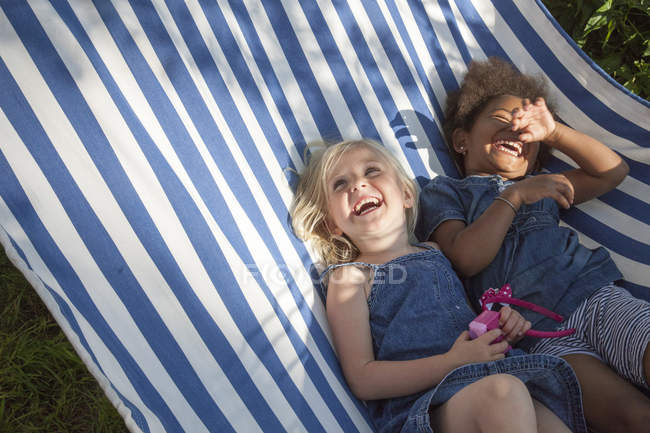 Two girls lying in striped hammock and laughing, selective focus — Stock Photo