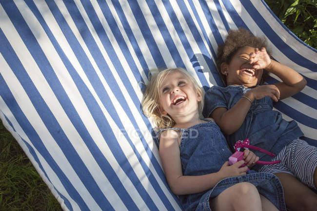 Дві дівчини, що лежать в смугастій гамаку і сміялися, селективний фокус — стокове фото