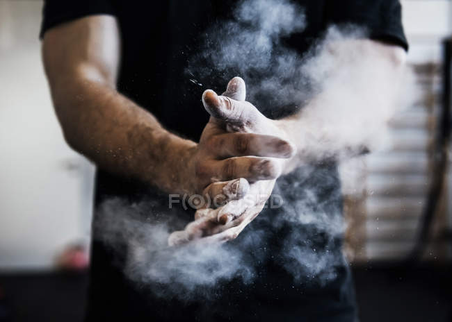 Man chalking hands in gym, close up — Stock Photo