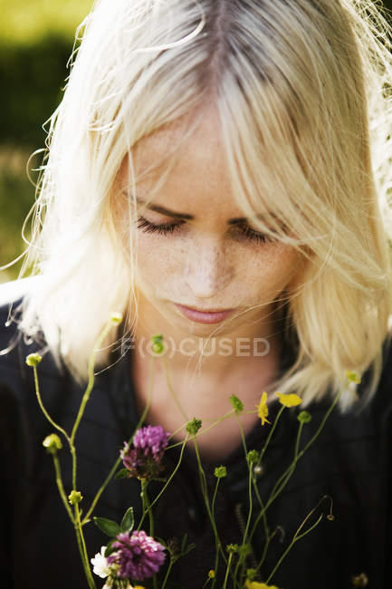 Young woman and wildflowers, focus on foreground — Stock Photo