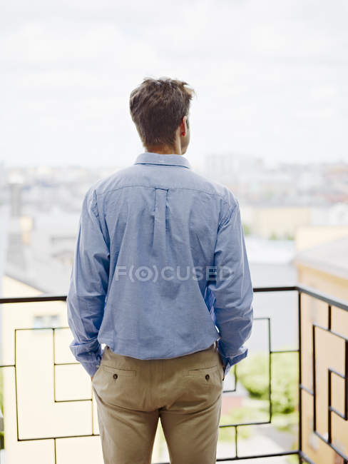 Заднього вигляду чоловік, дивлячись на вид з балконом — стокове фото