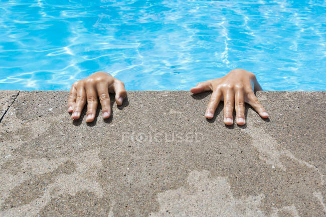 Wet hands on edge of swimming pool — Stock Photo