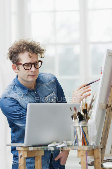 Man looking at laptop while painting at easel — Stock Photo