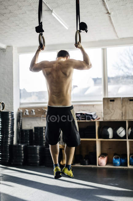 Young man training on gymnastic rings — Stock Photo