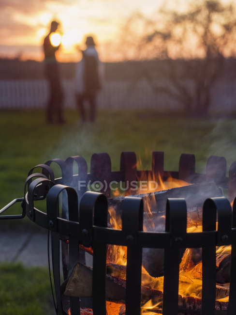 Brazier with burning wood, silhouettes of man and woman in background — Stock Photo