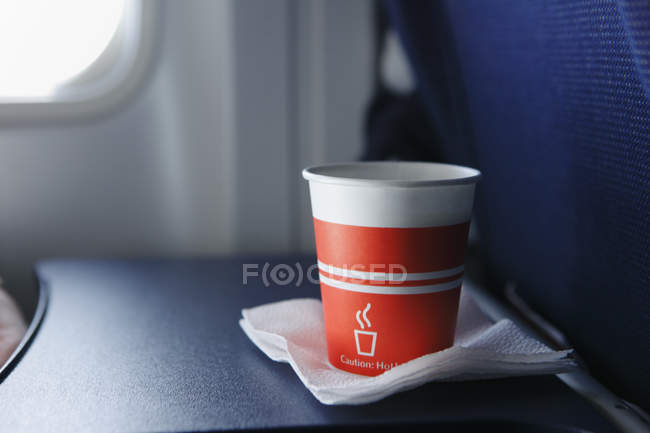 Disposable cup on airplane table, close up shot — Stock Photo