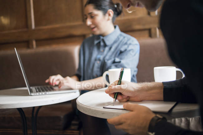 Young people working in cafe, differential focus — Stock Photo