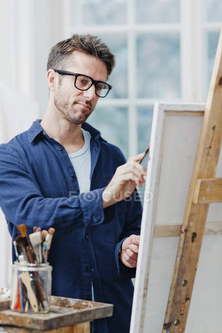 Man wearing eyeglasses painting at easel — Stock Photo