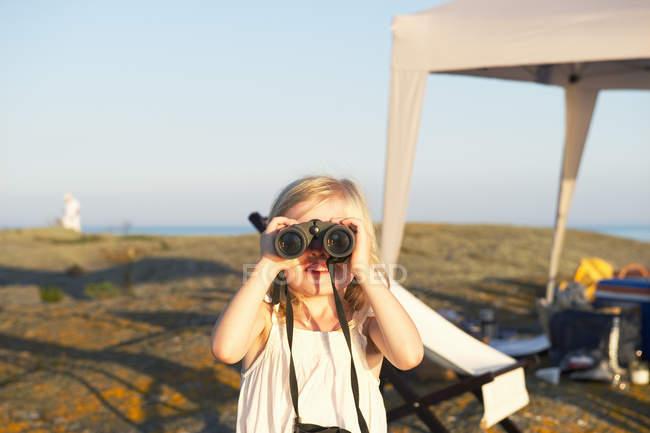 Little girl looking through binoculars at beach — Stock Photo