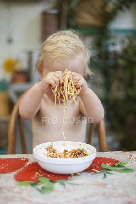 Мальчик играет со спагетти, избирательный фокус — стоковое фото