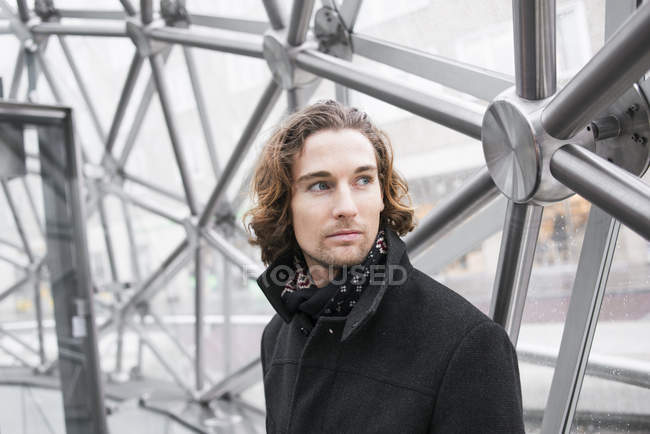 Portrait of young man with wavy hair looking away — Stock Photo