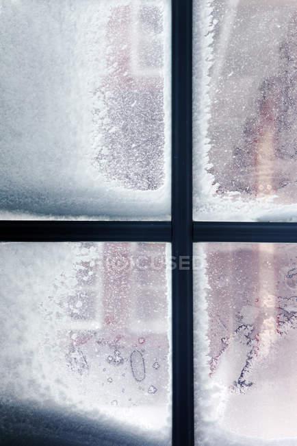 Fenêtre recouverte de givre et de neige vus de l'intérieur — Photo de stock