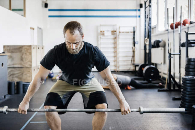 Young bearded man weightlifting in gym — Stock Photo