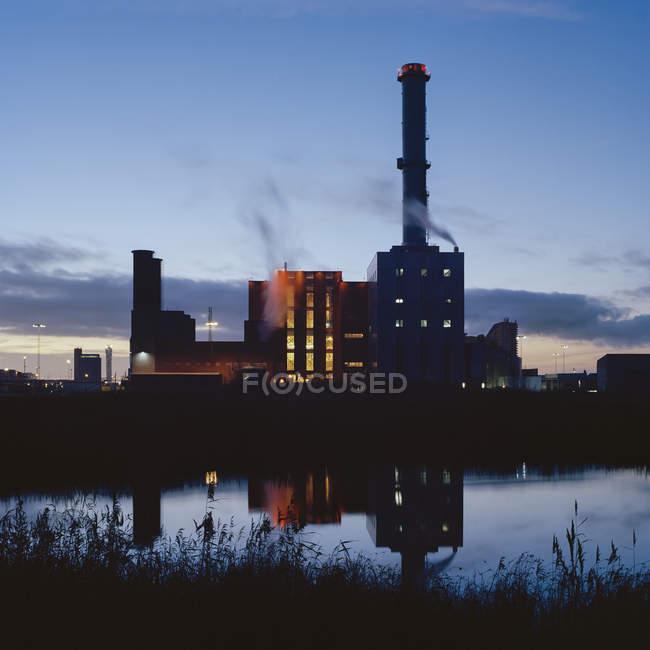 Industriebauten mit nachts im Wasser reflektierenden Rohren — Stockfoto