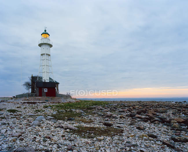 Low angle view of lighthouse against sky with clouds — стокове фото