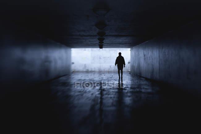 Женщина ночью в тёмном туннеле, избирательный фокус — стоковое фото