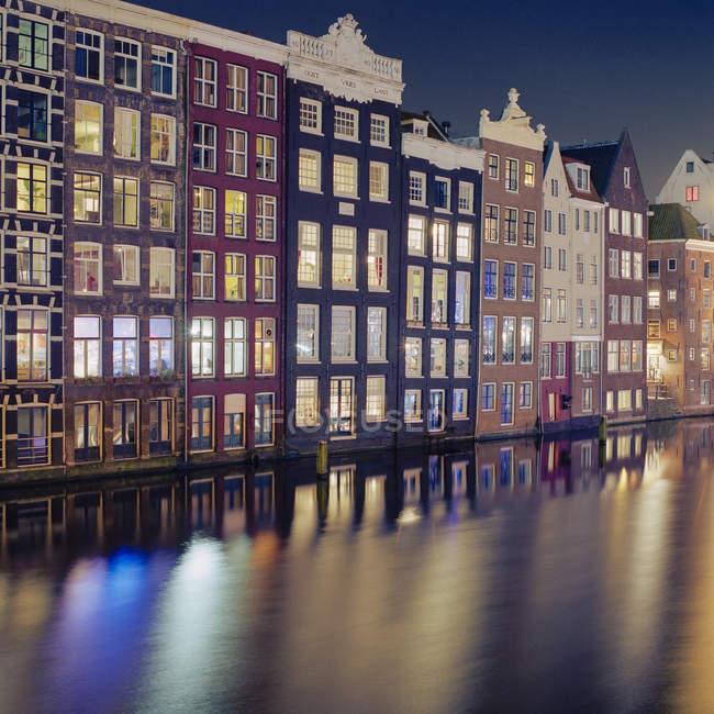 Edificios residenciales en el canal de agua borrosa, Amsterdam - foto de stock