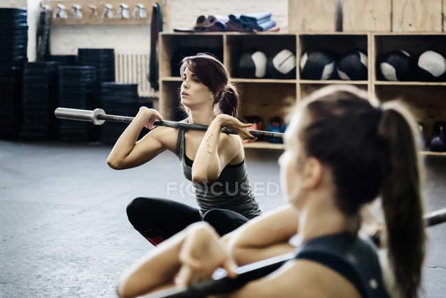 Dos mujeres jóvenes, entrenamiento con pesas en gimnasio - foto de stock