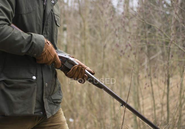 Sección media del hombre con la pistola en el bosque - foto de stock