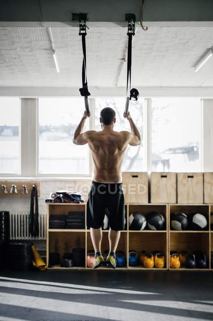 Junger Mann Training auf Gymnastik Ringen — Stockfoto