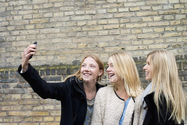 Attractive young women making selfie in front of brick wall at university campus — Stock Photo