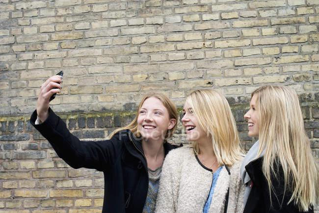 Attraktive junge Frauen machen Selfie vor Mauer am Uni-campus — Stockfoto