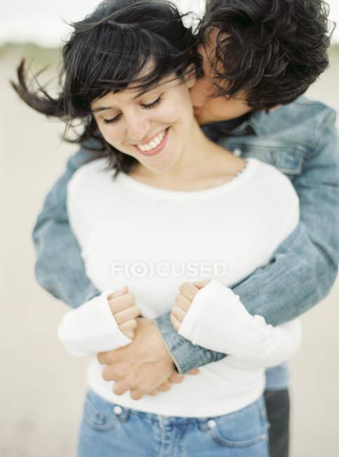 Noivo que abraça e que beija a amiga, foco no primeiro plano — Fotografia de Stock