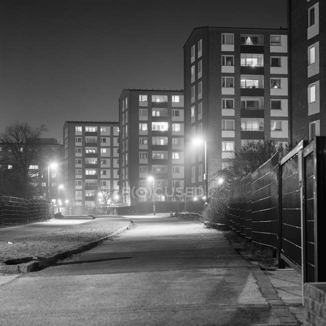 Residential district buildings illuminated at night, black and white — Stock Photo