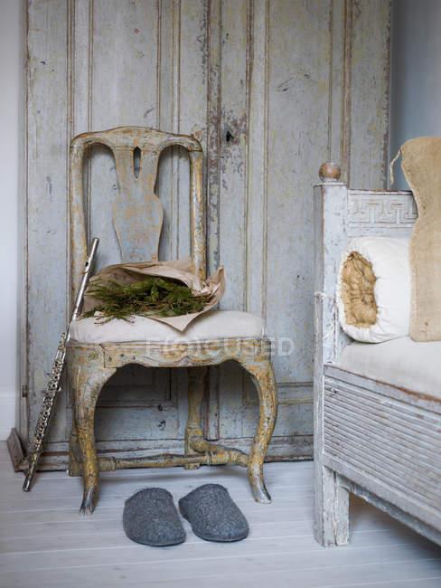 Деревенском стул, флейта, Тапочки и сосновых ветвей рядом с диваном — стоковое фото
