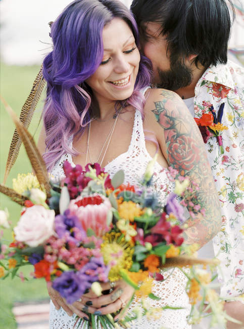Groom kissing bride at hippie wedding, focus on foreground — Stock Photo