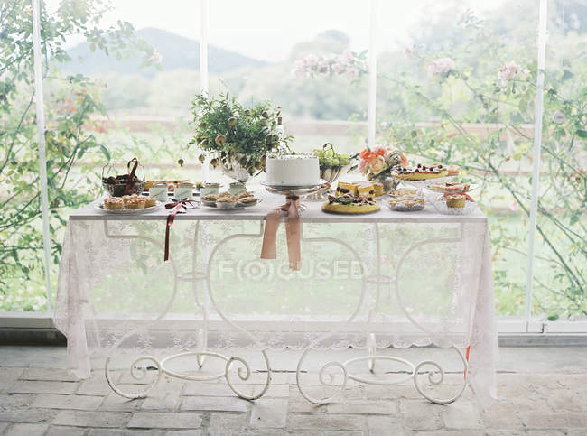 Table served with cakes and potted plant — Stock Photo