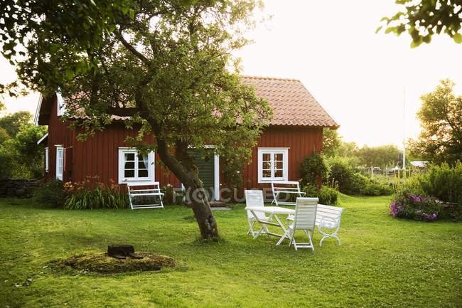 Falu rotes Ferienhaus mit Tisch und Stühlen auf grünem Rasen — Stockfoto