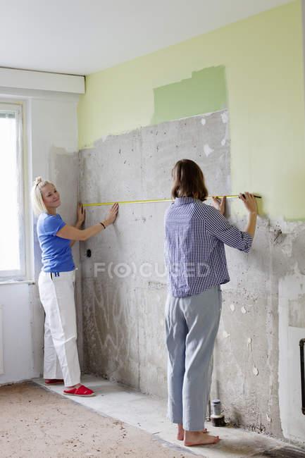 Молодые женщины измеряют стену для ремонта — стоковое фото