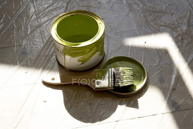 Can of green paint and paint brush on floor — Stock Photo