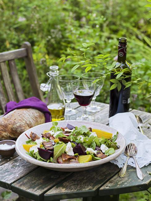 Козий сыр салат, хлеб, оливковое масло, соль, столовые приборы и вина на столе — стоковое фото