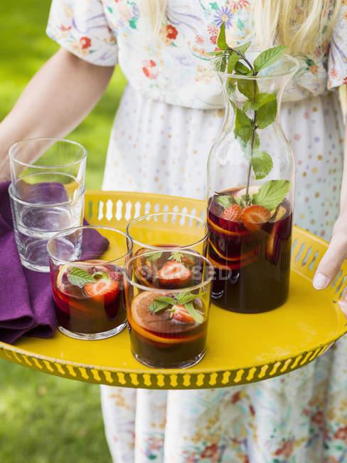 Mulher segurando uma bandeja amarela com jarra e copos de sangria — Fotografia de Stock
