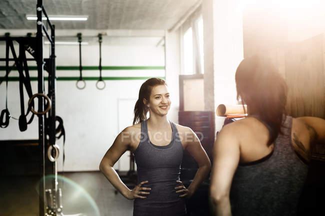 Два молодих жінок, що стояли лицем до лиця і усміхнений в тренажерний зал — стокове фото