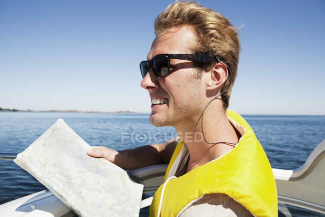 Молодой человек, держащий карта, фокус на переднем плане — стоковое фото