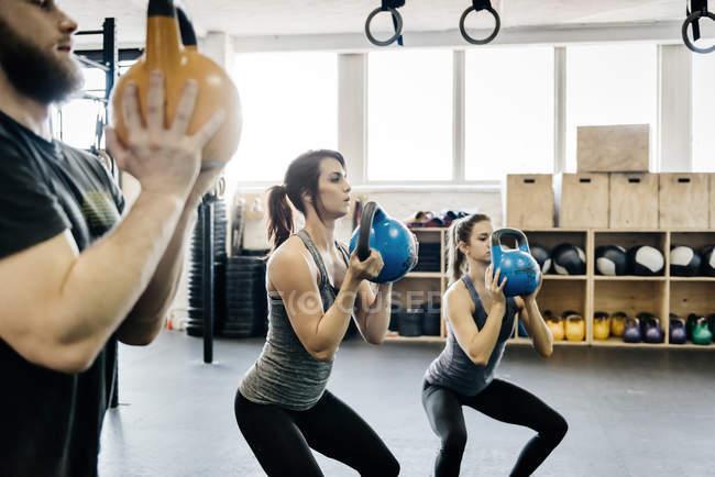Mujeres jóvenes y hombre cruzan el entrenamiento con timbres en el gimnasio - foto de stock