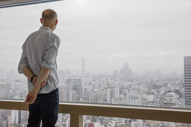 Чоловік дивиться на міський пейзаж через вікно — стокове фото