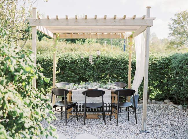 Vue de face de la table sous belvédère dans le jardin — Photo de stock