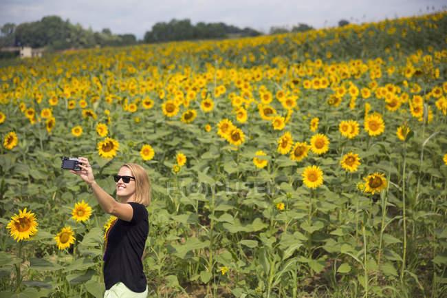 Femme prenant selfie contre champ de tournesol — Photo de stock