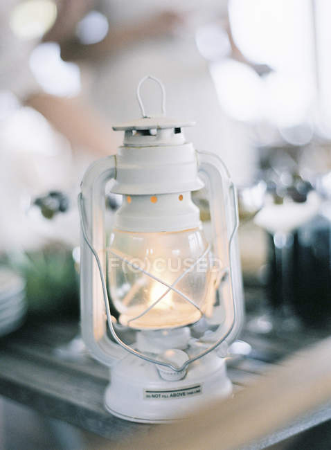Lit up small white lantern on table — стокове фото